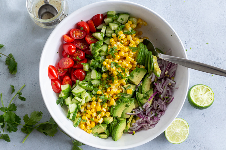 Corn tomato Avocado salad in a bowl with dressing next to it