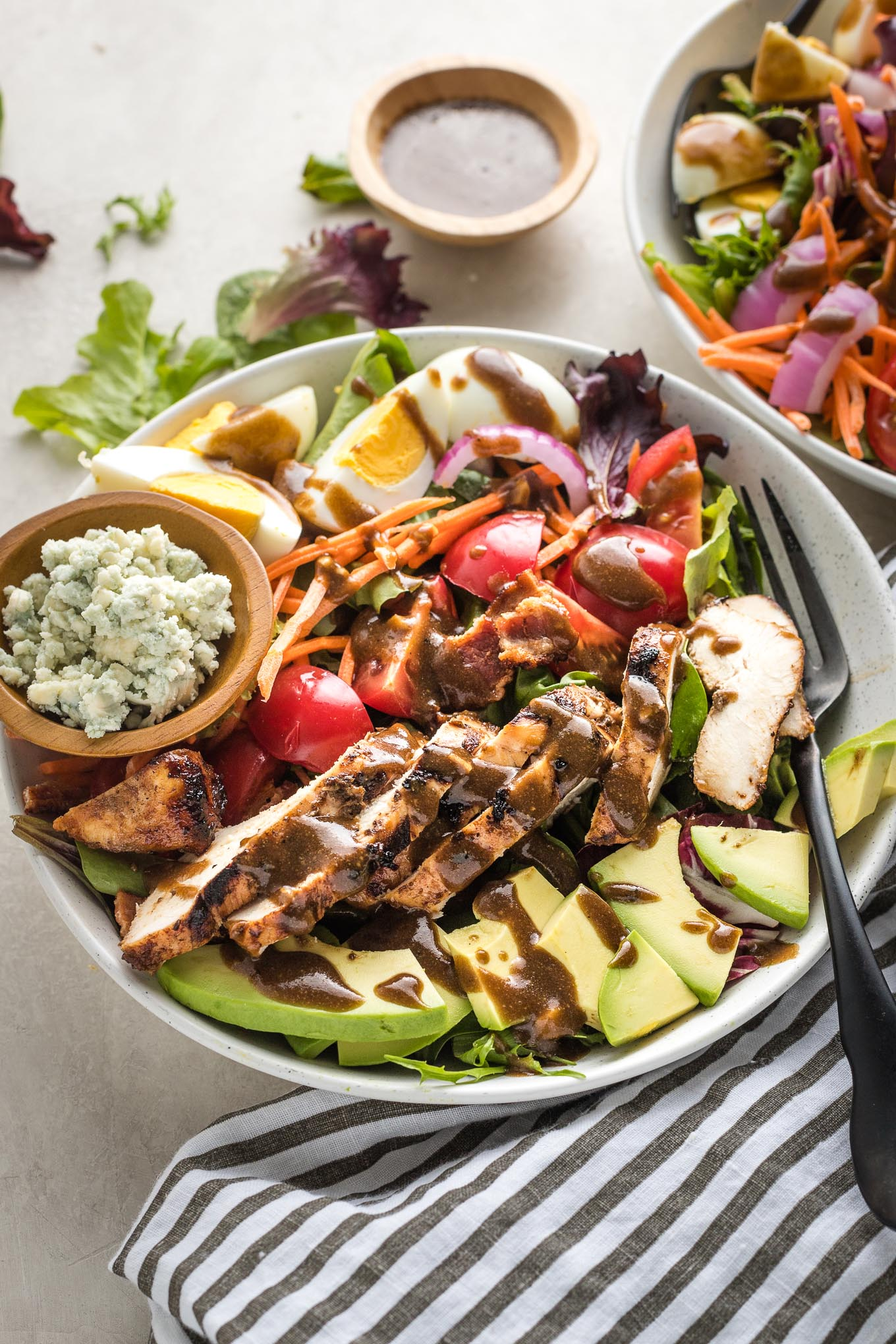 Cobb salads in white bowls served with grilled chicken and balsamic vinaigrette.