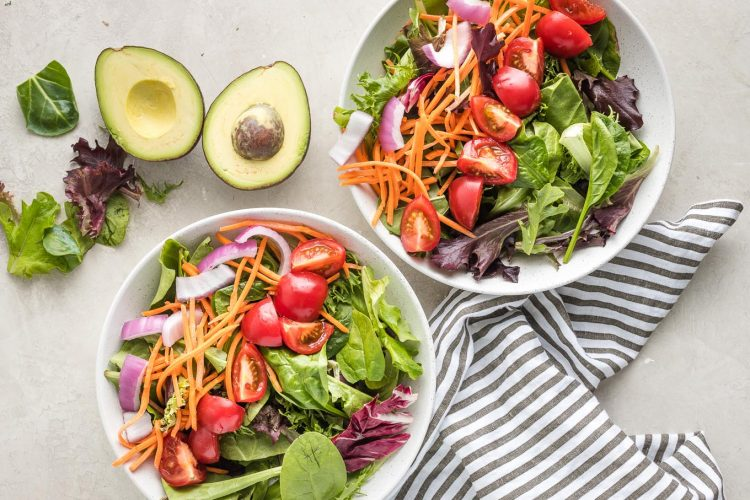 Greens, carrots, and cucumber in bowls.