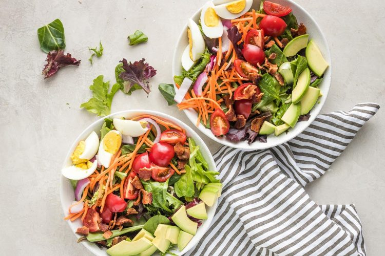 Salad bowls with hard-boiled eggs and avocado added.