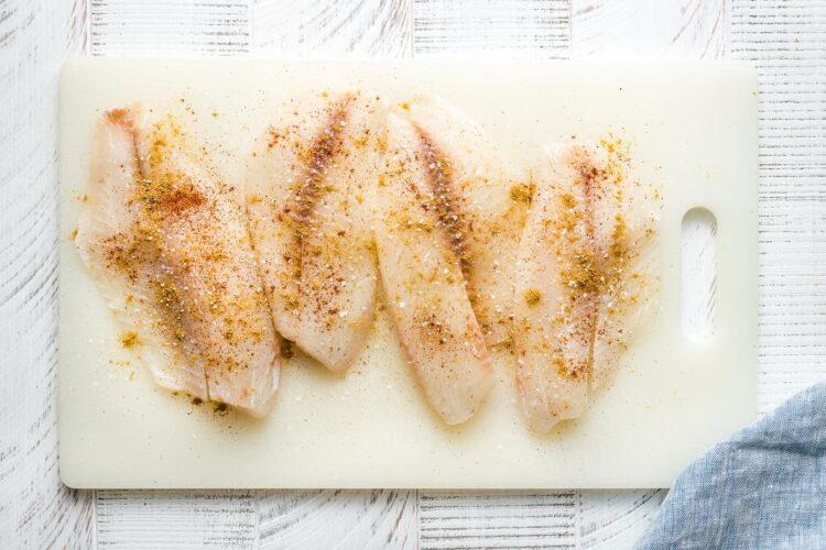 Seasoned tilapia filets on a white cutting board.