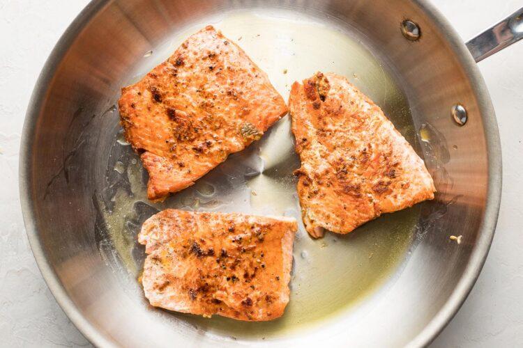 Pan-seared salmon filets in a skillet.