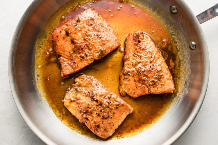 Seared salmon filets with sauce in skillet.